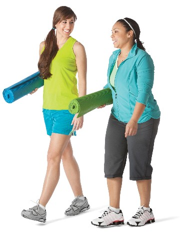 Two women walking and holding yoga mats