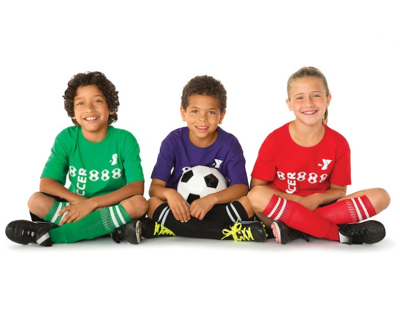 Three children wearing soccer attire with a soccer ball